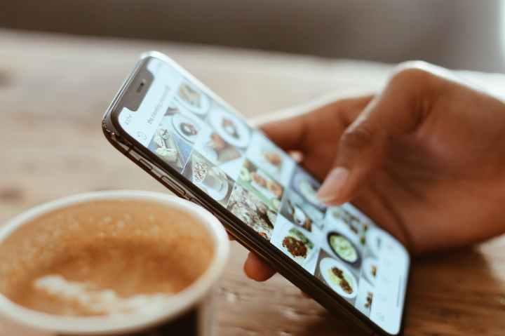 Una mano femminile con uno smartphone, di fianco ad una tazza di caffè.