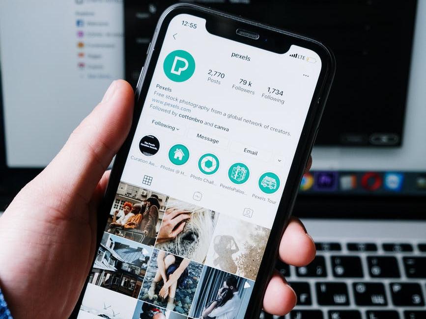 Una mano impugna uno smartphone mostrano il proprio profilo Instagram e le copertine dei contenuti in evidenza, anche detti Instagram Highlights