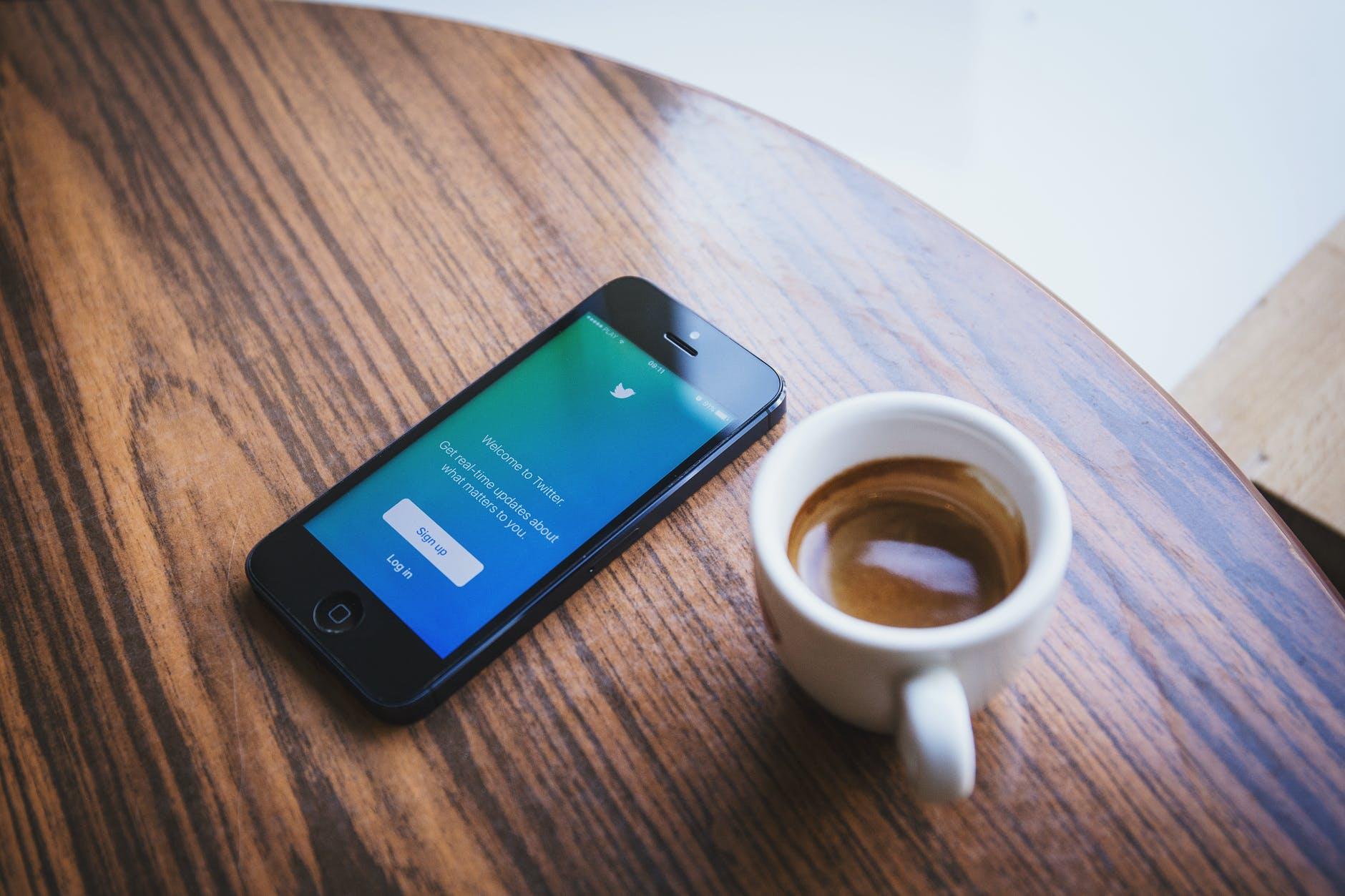 Uno smartphone ed una tazzina di caffè su un tavolino di legno con venature marrone scure