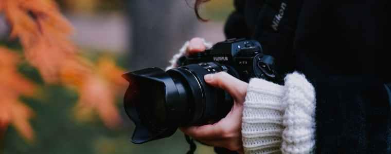 Una macchina fotografica professionale fra le mani di una giovane donna con maglione e giaccone.
