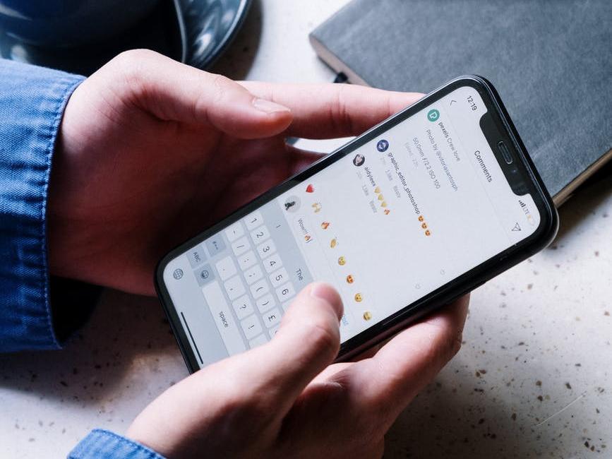 Ragazzo risponde ai commenti ricevuti sui social attraverso il proprio smartphone