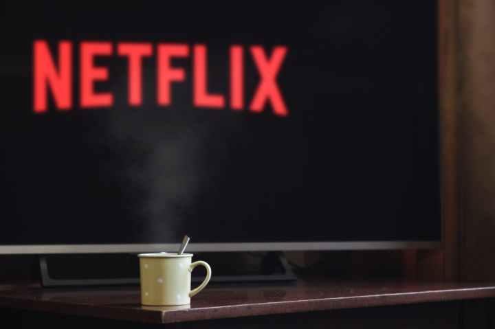 Una tazza con cucchiaino, davanti alla tv con il logo Netflix in rosso